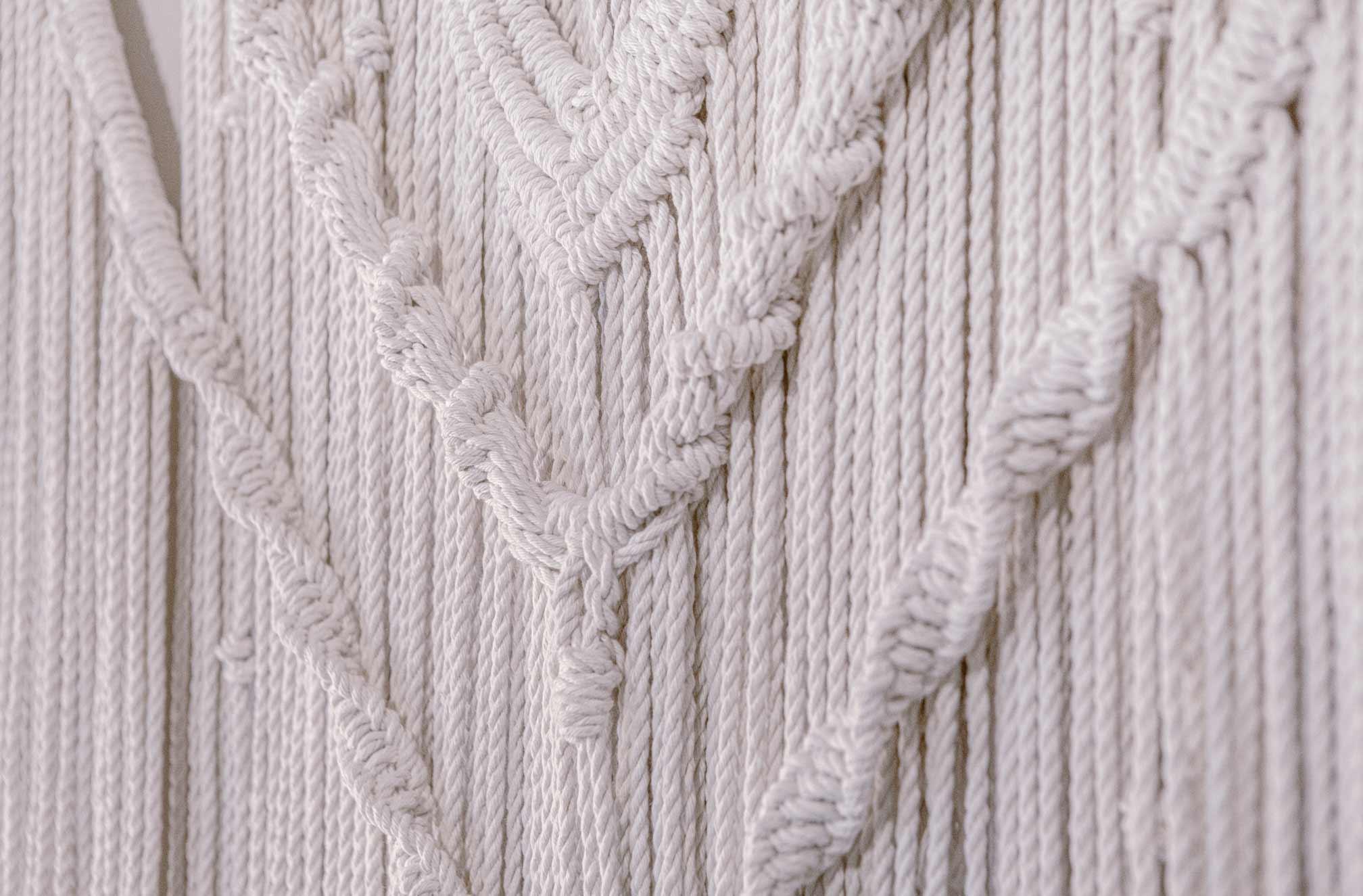 Detalle de nudos parte media de tapiz artesanal de macramé hecho con algodón orgánico y materiales sostenibles
