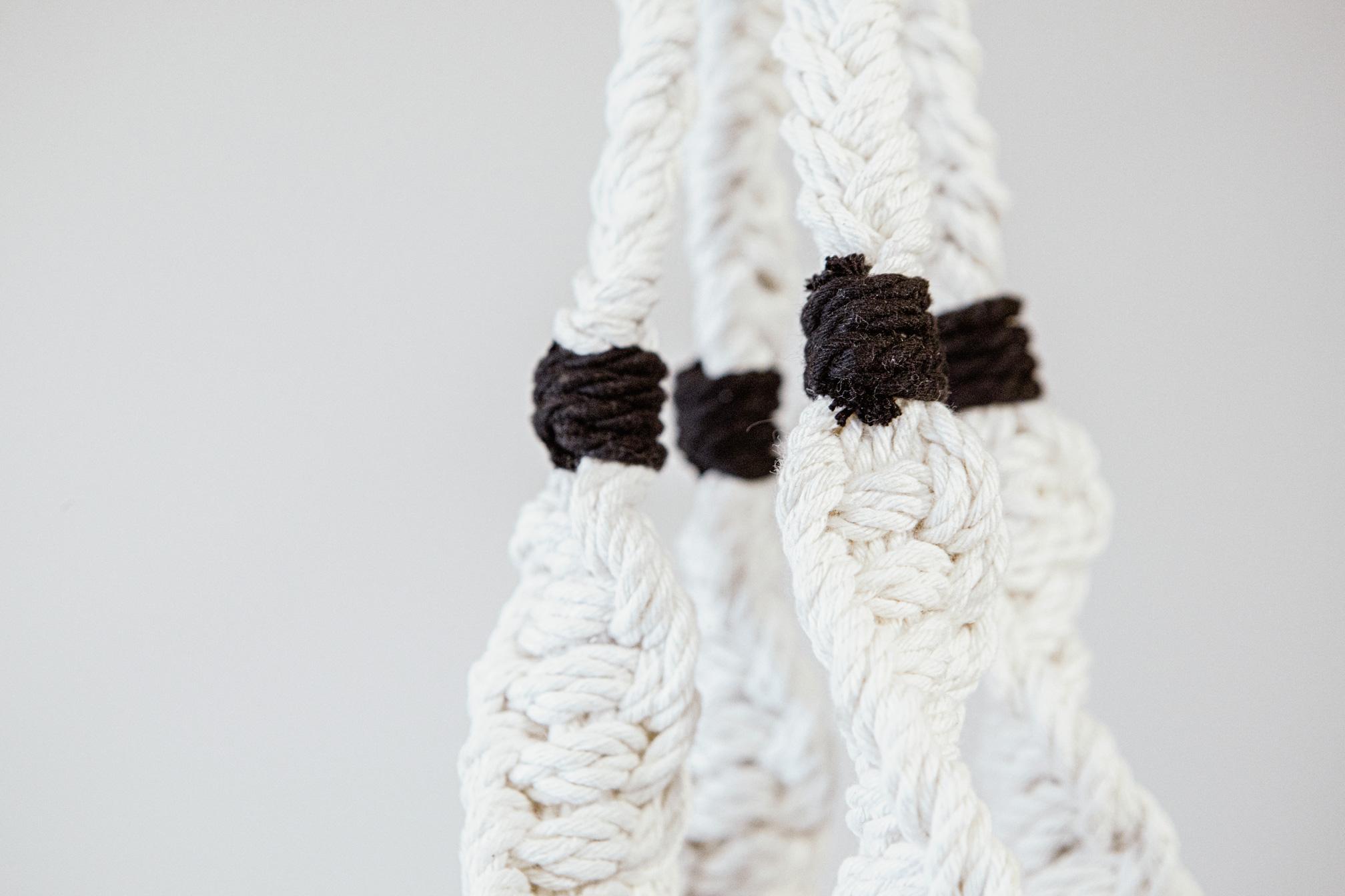 Detalle de macetero artesanal de macramé fabricado en algodón ecológico en color crudo con detalles negros