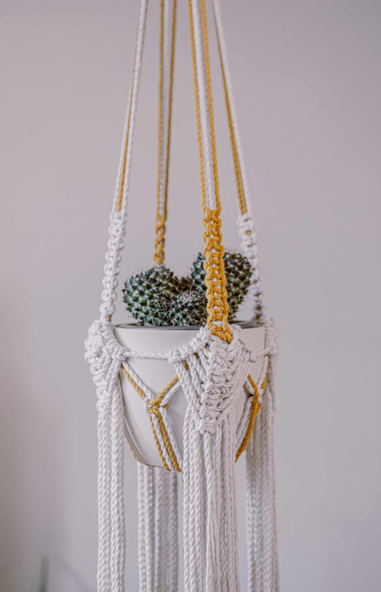 Detalle del macetero artesanal de macramé hecho de algodón ecológico en color crudo y mostaza