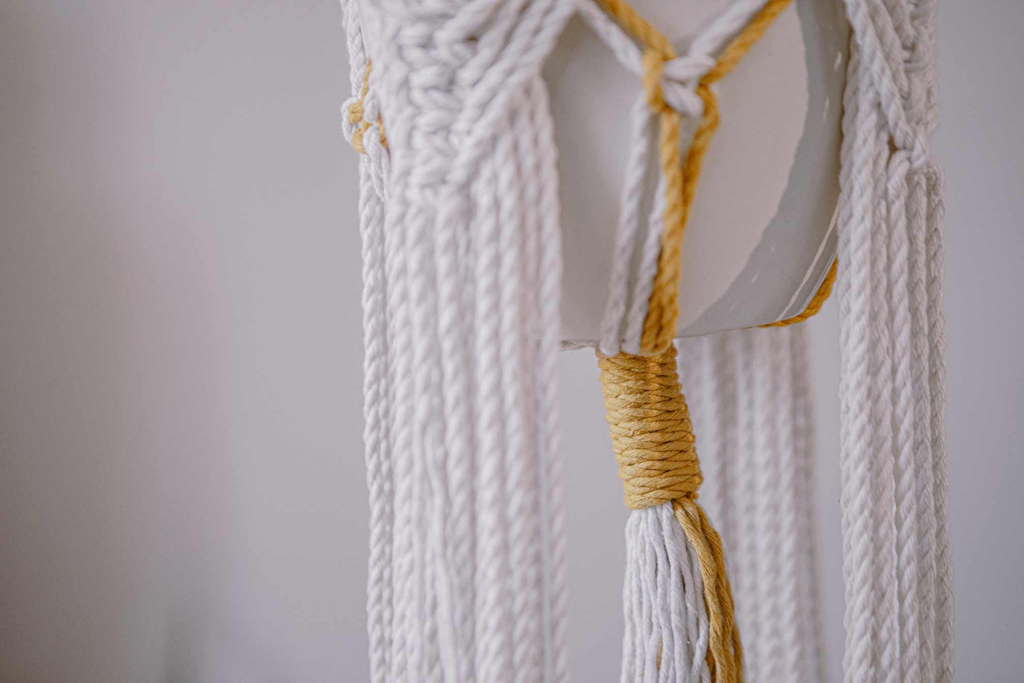 Detalle zona baja de un macetero artesanal de macramé hecho de algodón ecológico en color crudo y mostaza