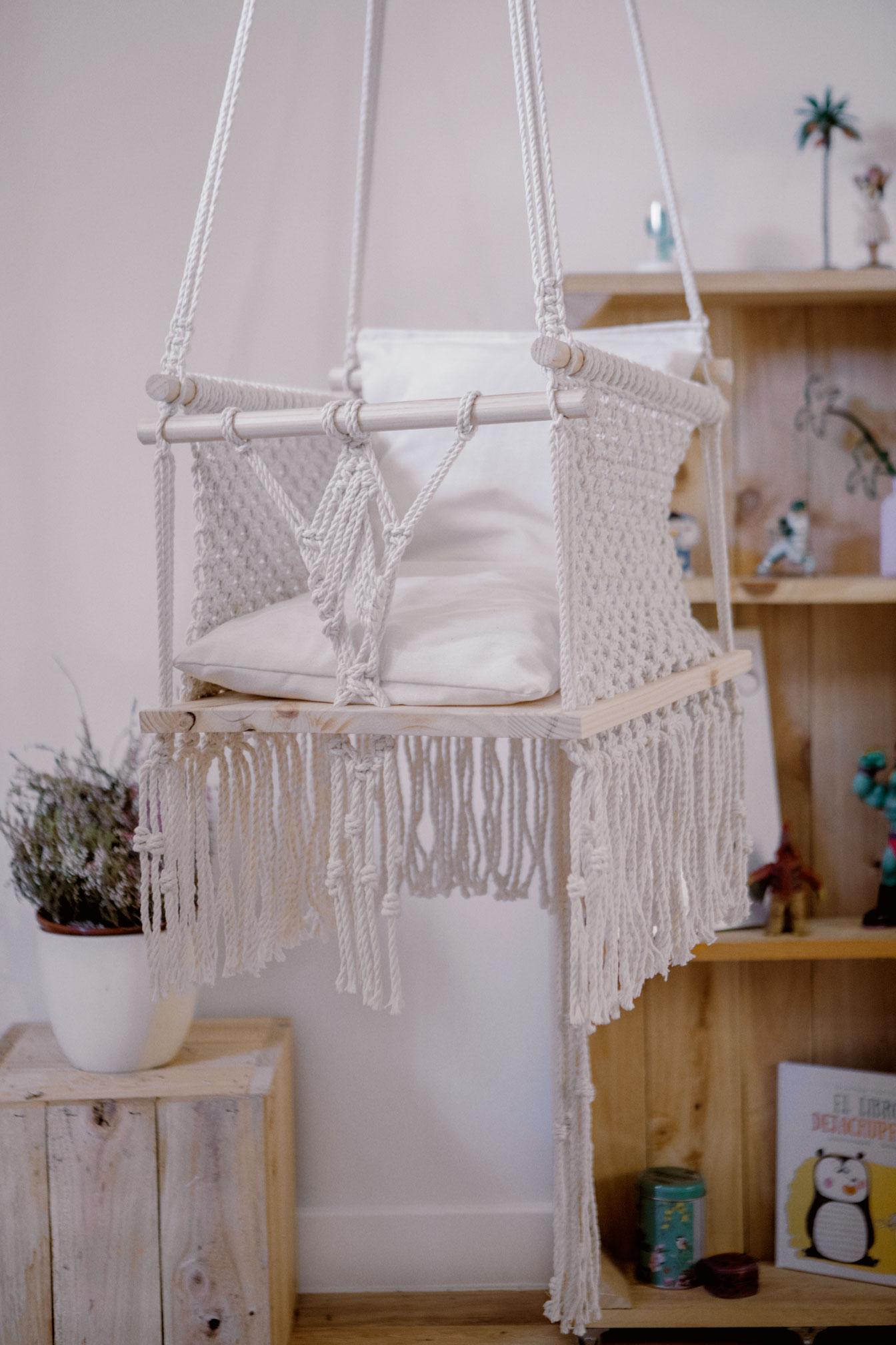 Detalle de silla infantil de macramé hecha a mano con materiales sostnibles y un cojín con respaldo relleno de guata