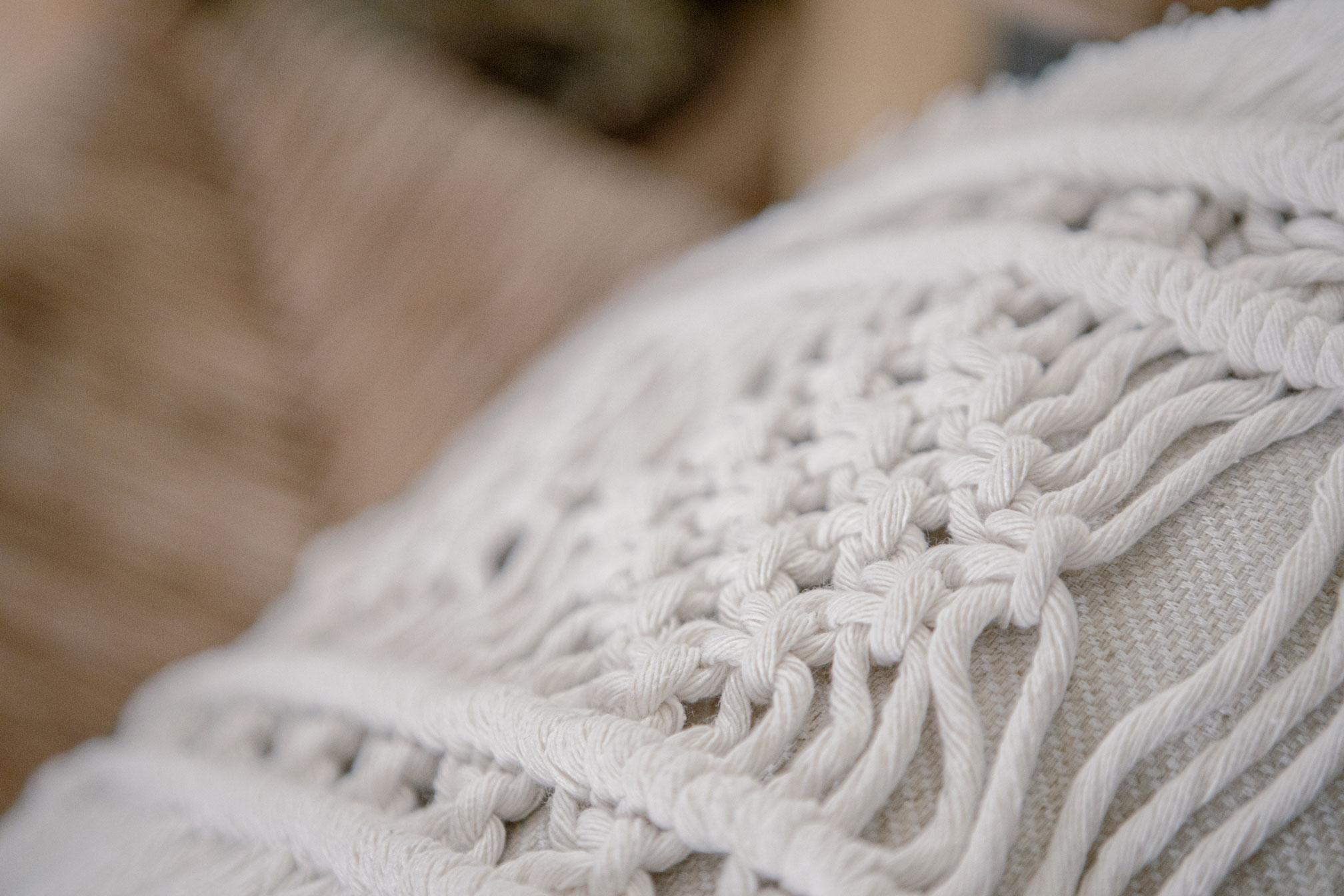 Detalle de cojín hecho de macramé en color crudo con algodón ecológico